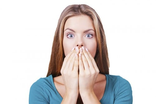 scared woman covering her mouth