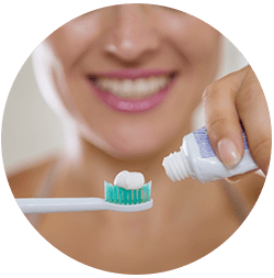 woman applying toothpaste to brush